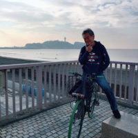 愛車フラミンゴ号と江ノ島をバックにポーズをとる柴田。笑